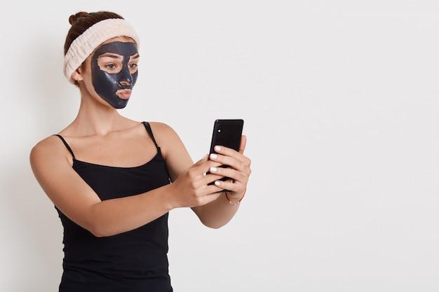 Retrato de uma jovem mulher feliz após o banho com faixa de cabelo na cabeça, com máscara preta, fica sobre uma parede branca, tomando selfie através de seu telefone móvel.