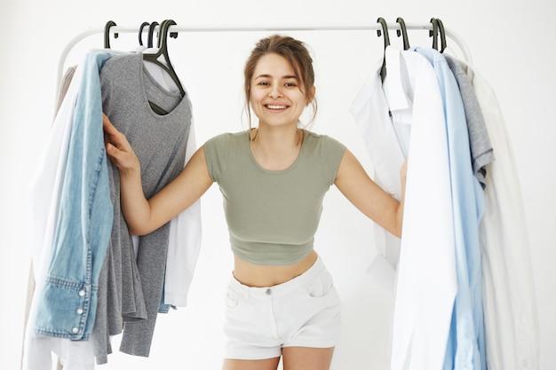 Retrato de uma jovem mulher feliz bonita olhando para o guarda-roupa de cabides sorrindo sorrindo para a câmera sobre a parede branca.
