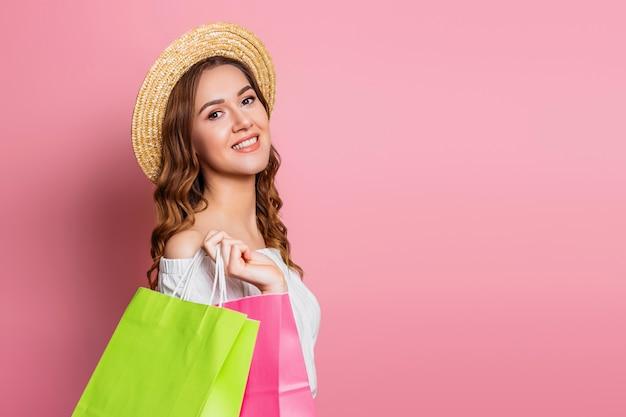 Retrato de uma jovem mulher feliz com cabelos ondulados em um chapéu de palha e um vestido vintage com sacolas verdes nas mãos em uma parede rosa. garota sorri e faz compras conceito de venda