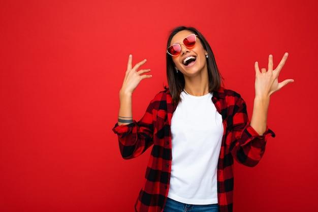 Retrato de uma jovem mulher feliz e positiva com emoções sinceras, vestindo camiseta branca