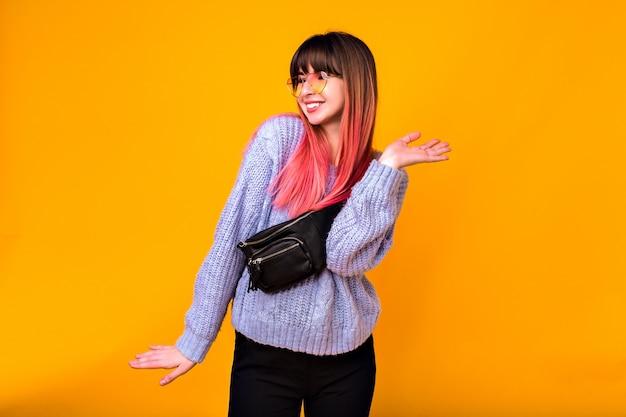 Retrato de uma jovem mulher feliz, emoções positivas saiu, cabelos fúcsia na moda brilhantes, camisola aconchegante, calças e bolsa de bumbum.