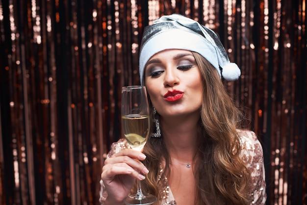 Retrato de uma jovem mulher feliz no chapéu de santa prata com taça de champanhe nas mãos.