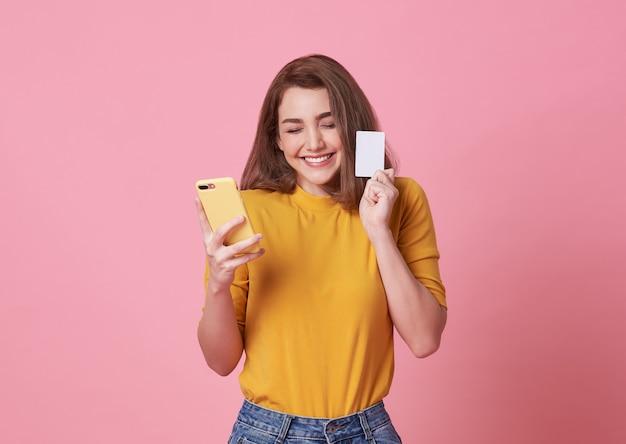 Retrato de uma jovem mulher feliz que mantém o telefone móvel e o cartão de crédito isolados sobre o rosa.