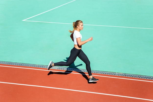 Retrato de uma jovem mulher fitness correndo no estádio