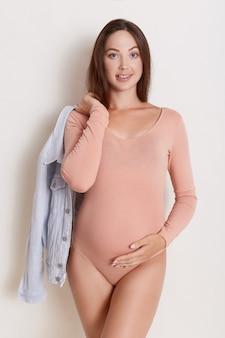 Retrato de uma jovem mulher grávida segurando a jaqueta jeans elegante na mão atrás das costas