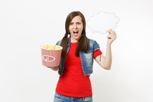 Retrato de uma jovem mulher irritada com roupas casuais, assistindo a um filme de cinema segurando uma nuvem com lugar para texto, copyspace e balde de pipoca isolado no fundo branco. emoções no conceito de cinema