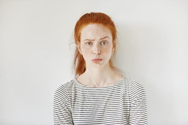 Retrato de uma jovem mulher irritada com sardas e lábios franzidos, tendo decepcionado olhar infeliz, carrancudo e beicinho. adolescente teimosa parecendo zangada ou irritada.