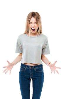 Retrato de uma jovem mulher irritada em pé e gritando