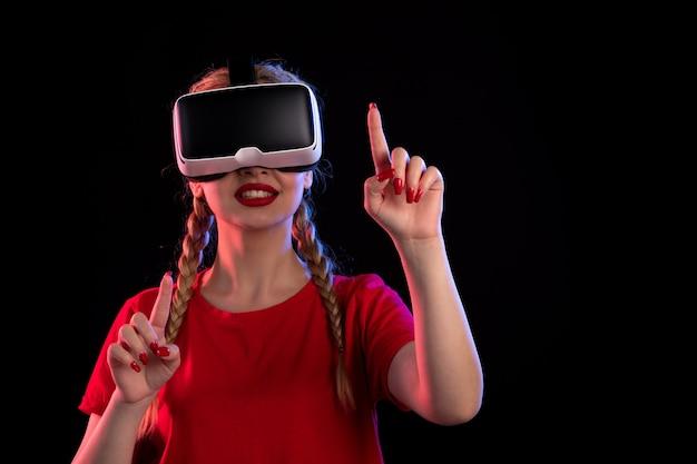 Retrato de uma jovem mulher jogando realidade virtual na parede escura