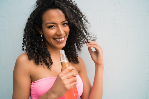 Retrato de uma jovem mulher latina afro-americana, desfrutando e bebendo uma garrafa de cerveja. conceito de estilo de vida.