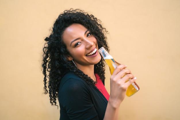 Retrato de uma jovem mulher latino-americana afro, desfrutando e bebendo uma garrafa de cerveja, contra um fundo amarelo. conceito de estilo de vida.