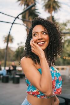 Retrato de uma jovem mulher latino-americana afro falando ao telefone, ao ar livre na rua. conceito de tecnologia.