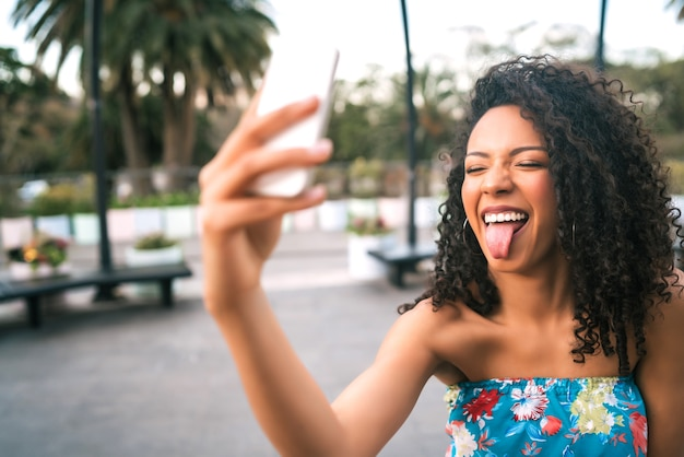 Retrato de uma jovem mulher latino-americana afro tomando uma selfie com telefone móvel ao ar livre na rua.