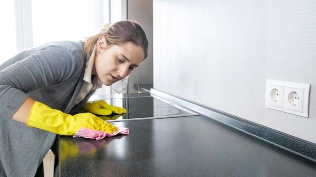 Retrato de uma jovem mulher, limpando e polindo a superfície e a bancada da cozinha enquanto trabalhava em casa.