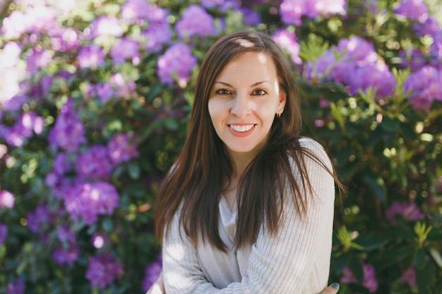 Retrato de uma jovem mulher linda sensual morena com sorriso encantador, vestindo roupas leves casuais. mulher sorridente perto de arbusto florido no parque da cidade ao ar livre na natureza da primavera. conceito de estilo de vida.