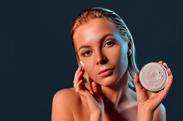 Retrato de uma jovem mulher loira atraente com pele radiante com creme para o rosto na parede preta