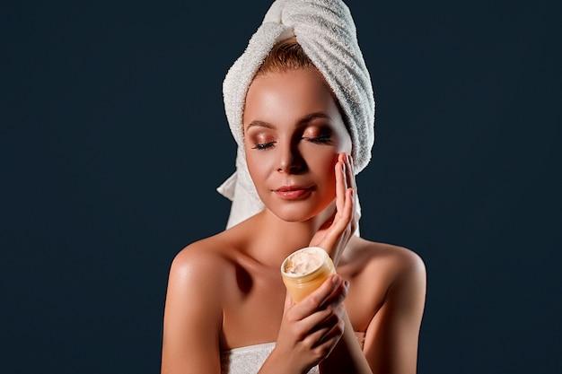 Retrato de uma jovem mulher loira atraente com uma toalha na cabeça com creme para o rosto na parede preta. .
