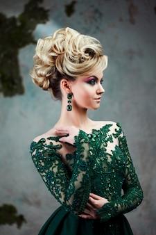 Retrato de uma jovem mulher loira atraente em um lindo vestido verde. plano de fundo texturizado, interior. penteado de luxo