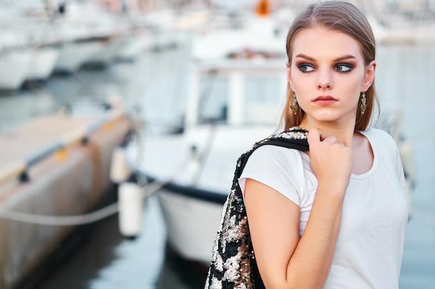 Retrato de uma jovem mulher loira atraente posando ao ar livre