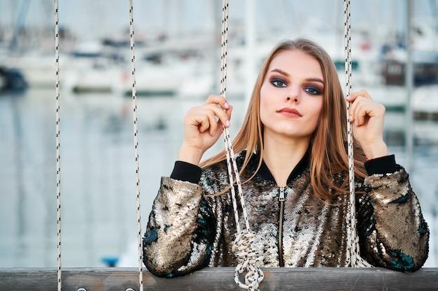 Retrato de uma jovem mulher loira atraente posando em um porto marítimo