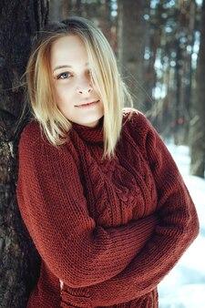 Retrato de uma jovem mulher loira bonita camisola posando em winter park. dia de sol na floresta.