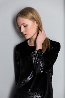 Retrato de uma jovem mulher loira bonita com maquiagem de noite em um vestido preto brilhante perto de uma parede cinza