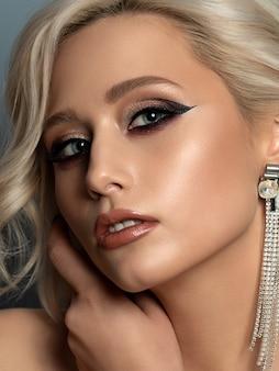 Retrato de uma jovem mulher loira bonita com maquiagem de noite tocando sua cabeça