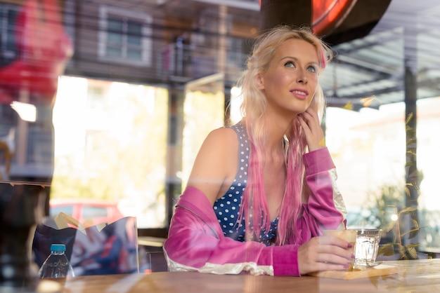 Retrato de uma jovem mulher loira bonita relaxando na cafeteria pela janela de vidro