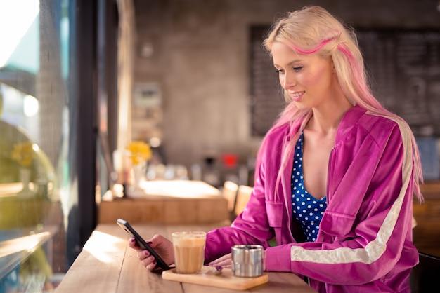 Retrato de uma jovem mulher loira bonita relaxando na cafeteria