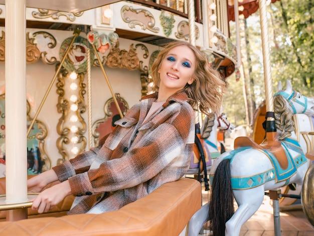 Retrato de uma jovem mulher loira com filha passando um bom tempo juntos no parque de diversões