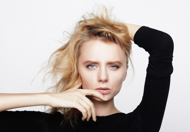 Retrato de uma jovem mulher loira com uma camisa preta em um fundo branco. uma mulher sem maquiagem. teste de modelo. modelo de moda.