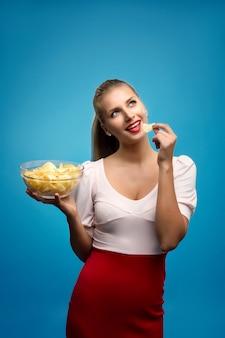Retrato de uma jovem mulher loira comendo batatas fritas e segurando uma tigela de vidro
