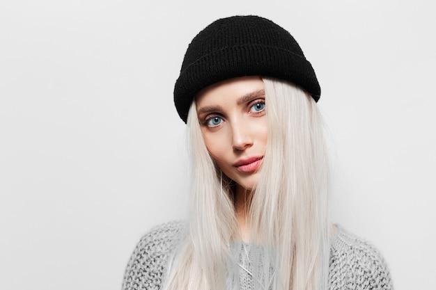 Retrato de uma jovem mulher loira de olhos azuis, usando o chapéu do beanie preto.