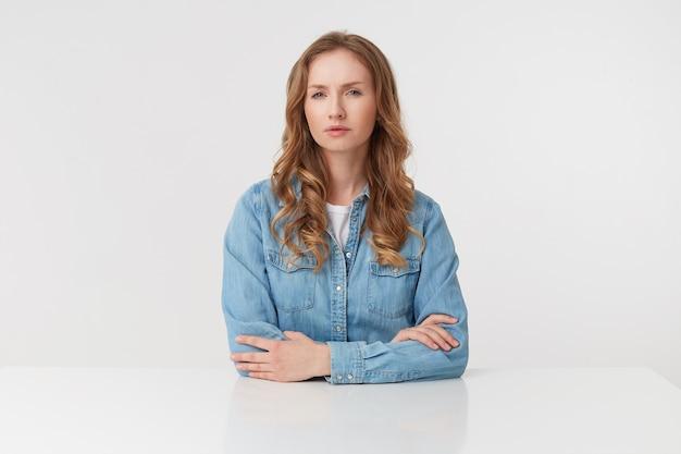 Retrato de uma jovem mulher loira descontente usa camisas jeans, sentado à mesa branca, isolada sobre fundo branco.