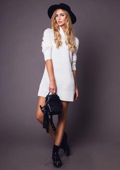 Retrato de uma jovem mulher loira elegante com chapéu e uma elegante camisola branca de inverno