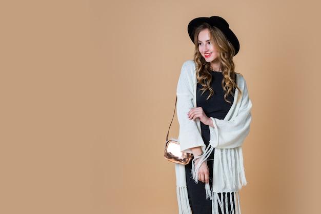 Retrato de uma jovem mulher loira elegante com um chapéu de lã preto usando um poncho grande de franjas brancas e um vestido longo cinza