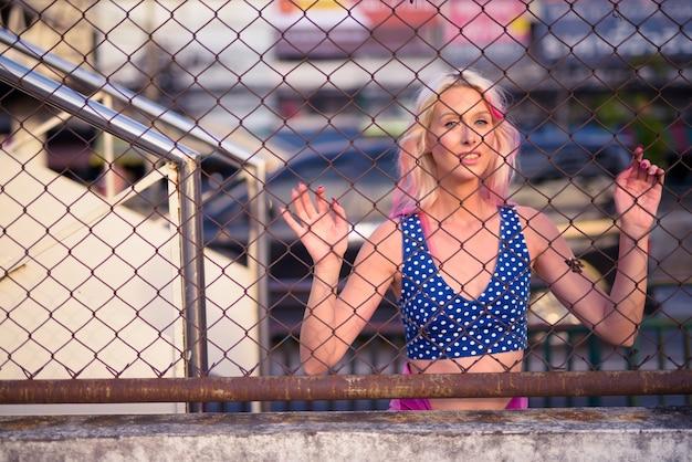 Retrato de uma jovem mulher loira explorando as ruas da cidade ao ar livre