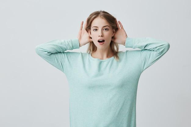 Retrato de uma jovem mulher loira segurando as mãos atrás das orelhas enquanto ouve uma história incrível