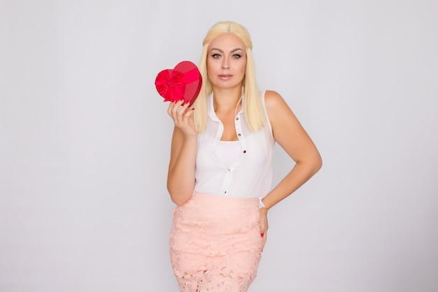 Retrato de uma jovem mulher loira segurando uma caixa de presente em forma de coração