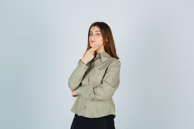 Retrato de uma jovem mulher mantendo os dedos no queixo na camisa