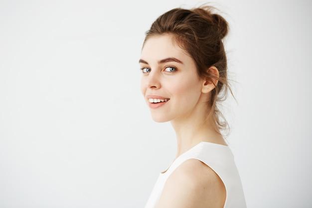 Retrato de uma jovem mulher morena bonita sorrindo de perfil.
