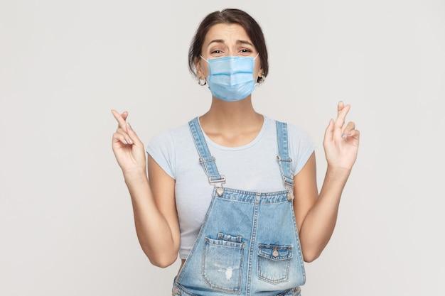 Retrato de uma jovem mulher morena esperançosa com máscara médica cirúrgica de macacão jeans em pé de braços cruzados, olhando para a câmera com rosto ansioso de preocupação. estúdio interno tiro isolado em fundo cinza.