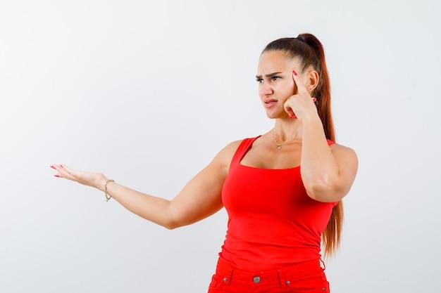 Retrato de uma jovem mulher mostrando algo em um top vermelho, calça e olhando pensativa para a frente