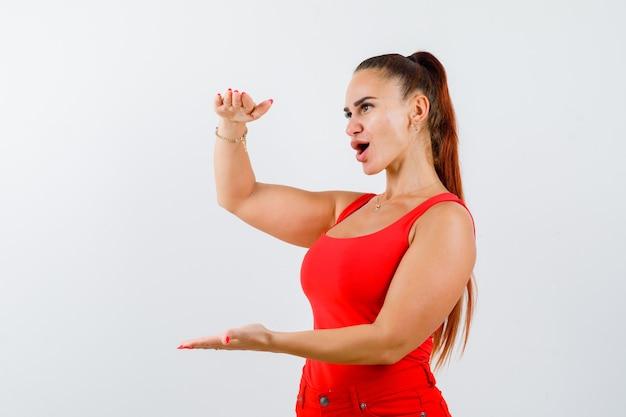 Retrato de uma jovem mulher mostrando sinal de tamanho em um top vermelho, calça e olhando confuso para a frente