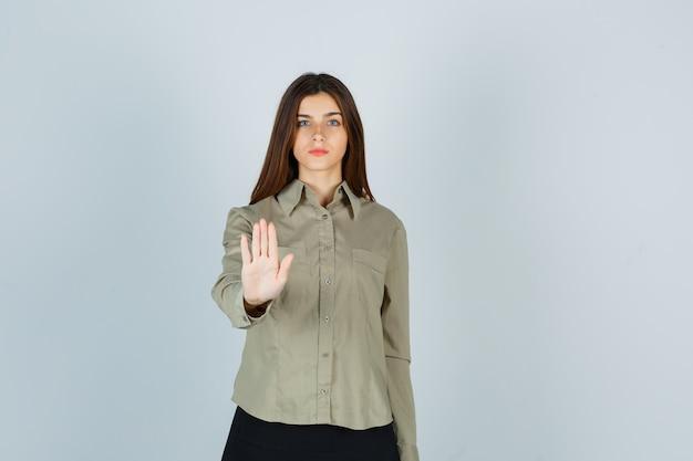 Retrato de uma jovem mulher mostrando um gesto de parada na camisa, saia e olhando sério.