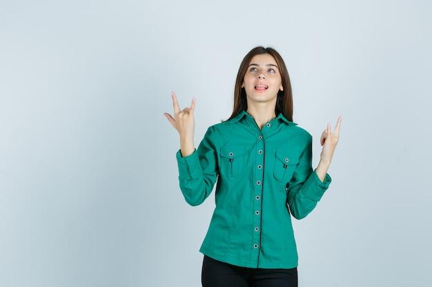 Retrato de uma jovem mulher mostrando um gesto de pedra, mostrando a língua em uma camisa verde e olhando para a frente