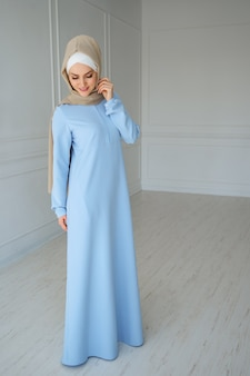 Retrato de uma jovem mulher muçulmana elegante em hijab bege e roupas tradicionais, posando no estúdio.