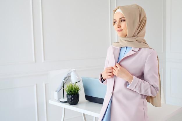 Retrato de uma jovem mulher muçulmana em hijab bege e roupas tradicionais, olhando para longe da câmera, copie o espaço.