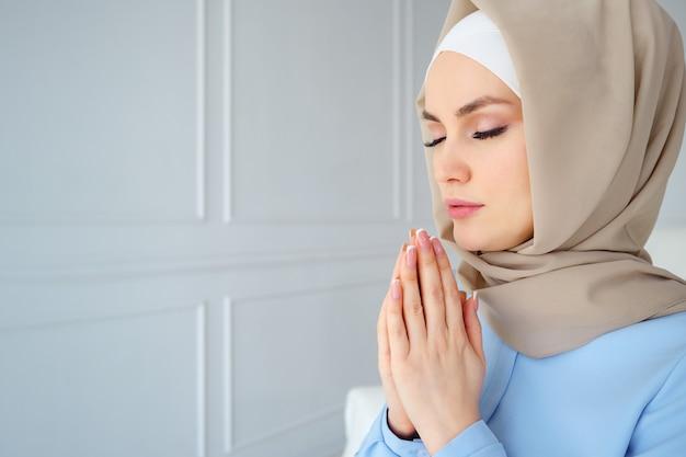 Retrato de uma jovem mulher muçulmana em hijab bege e roupas tradicionais, orando com os olhos fechados, copie o espaço.