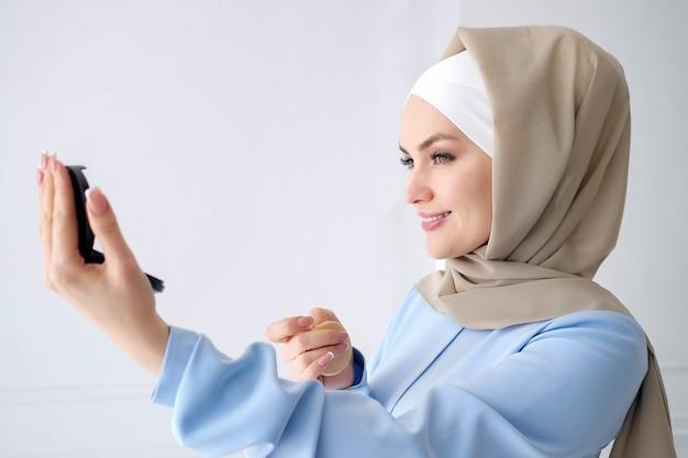 Retrato de uma jovem mulher muçulmana em hijab bege e vestido azul tradicional, olhando para o pequeno espelho em casa, vista lateral.